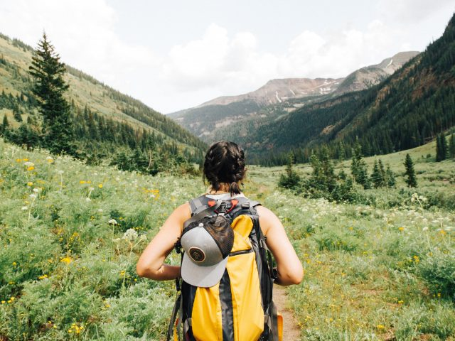 Woman hiking in grassy hills with yellow backpack