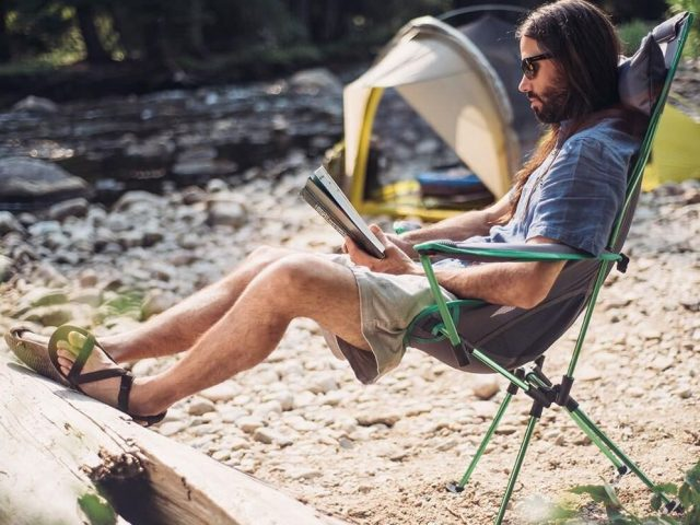 a man sitting and reading a book in a camp chair