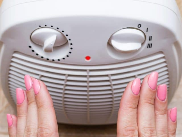 Female warms her cold hands near an electric heater at home. Selective focus, part of body.