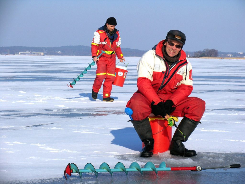 Two men in red jackets ice fishing with augers
