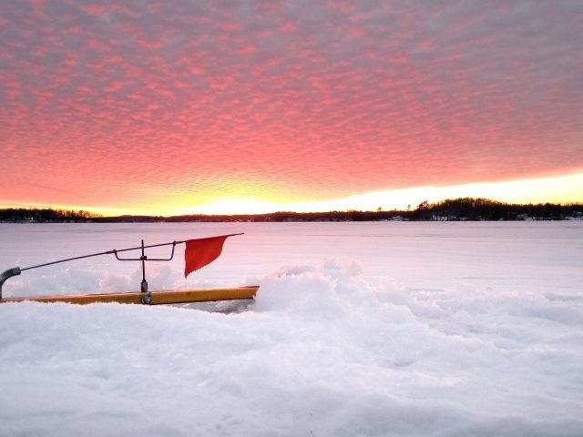 Wood ice fishing tip up on frozen lake with red flag