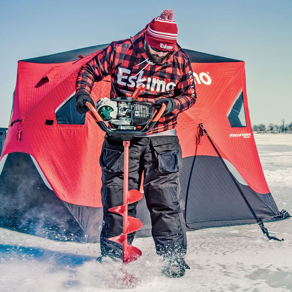 Man using red Eskimo gas powered auger to cut ice fishing holes in front of red ice shelter