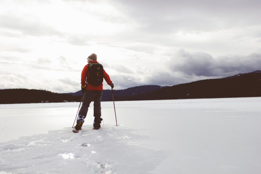 Man in red jacket snowshoeing across a frozen lake