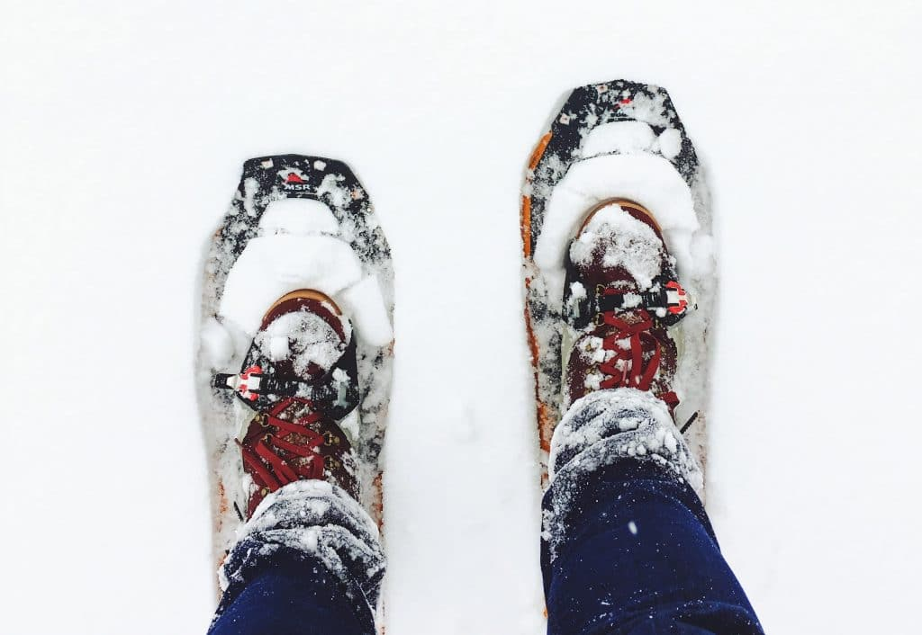 Boots with red laces on snowshoes in the snow