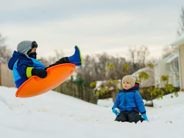 Children sledding with orange sled