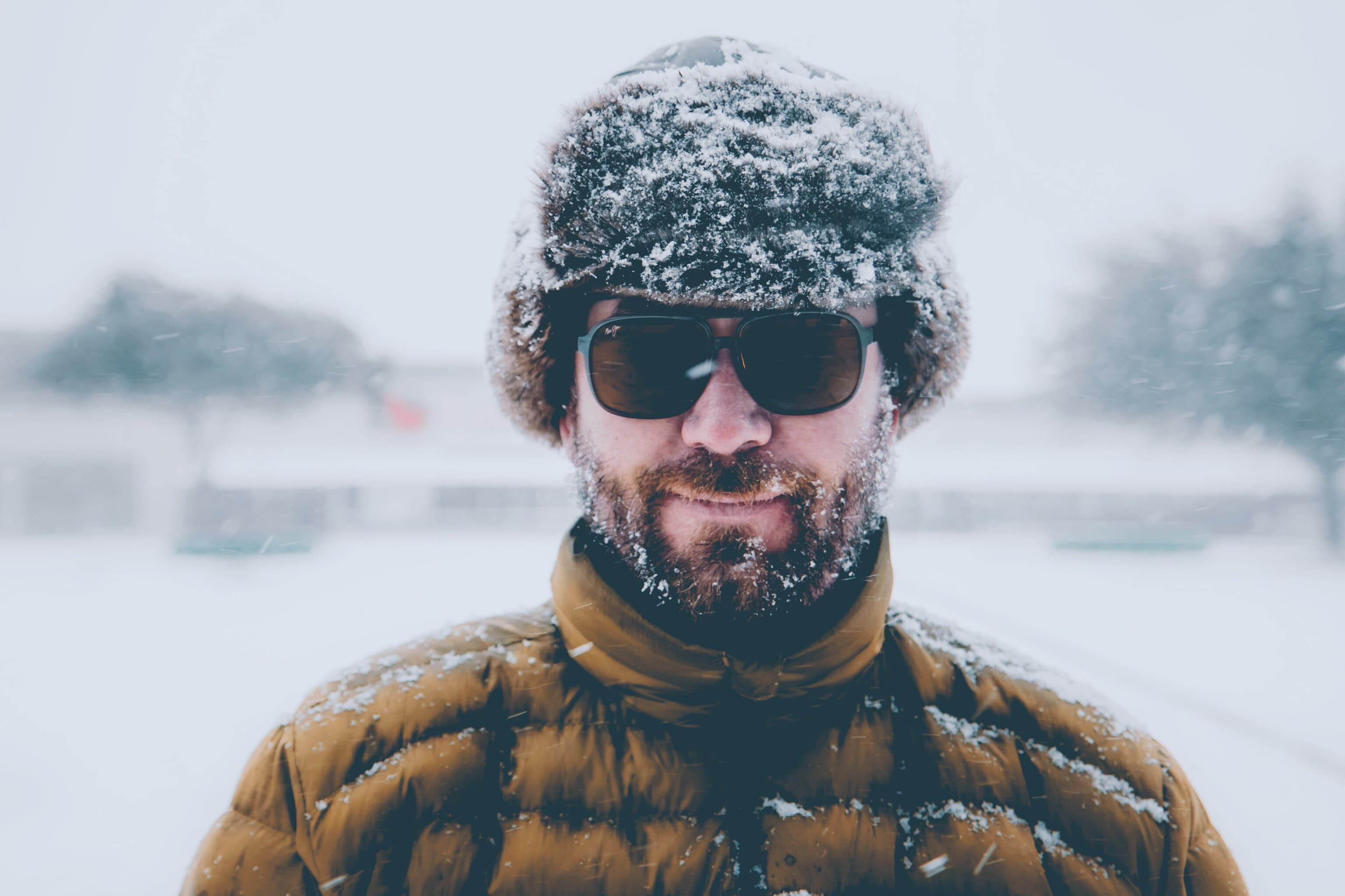 Man in furry hat with sunglasses in the snow