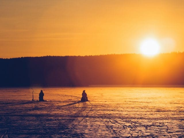 Two men ice fishing at sunset