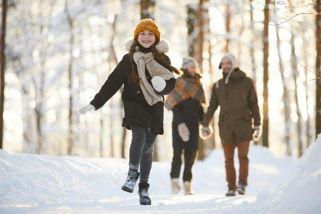 Full length portrait of happy little girl running towards camera in winter forest while enjoying walk with family, copy space