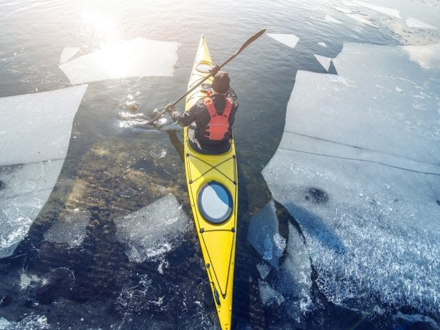 man kayak is on a frozen river