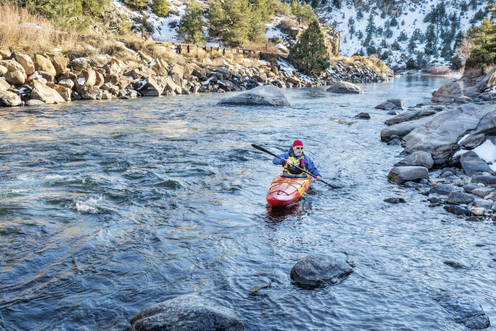 senior kayaker in a whitewater kayak paddling upstream of Arkansas River above Hecla Junction, Colorado in winter scenery (senior kayaker in a whitewater kayak paddling upstream of Arkansas River above Hecla Junction, Colorado in winter scenery, ASCII