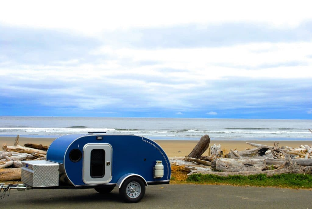 A blue teardrop camping trailer on the roadside along the Oregon Coast