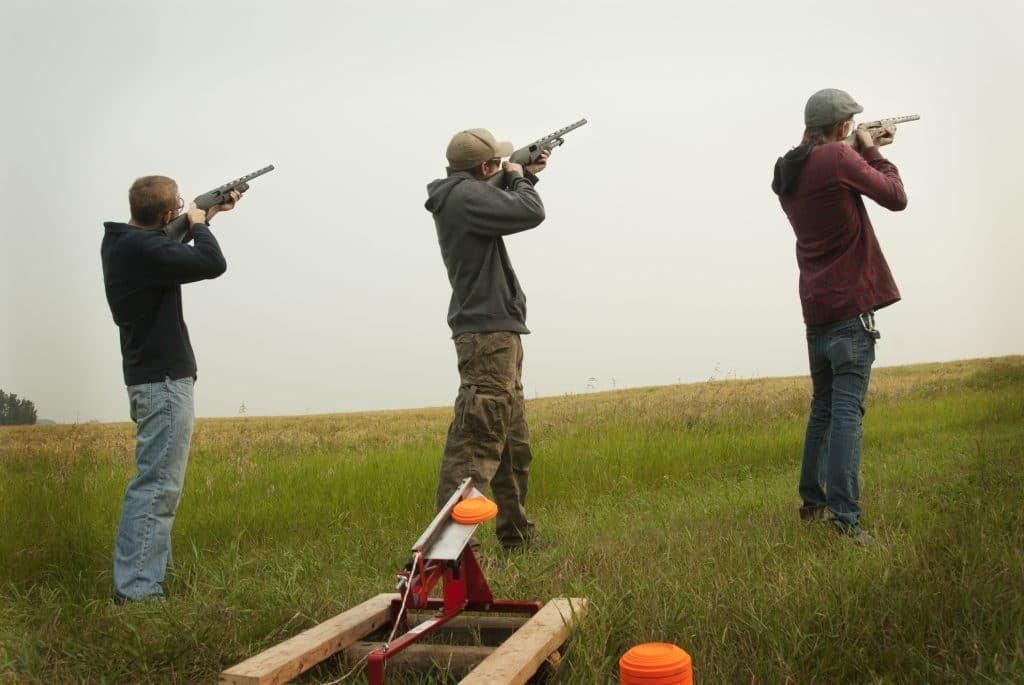 Three men target practising with clay pigeons, on a cloudy day