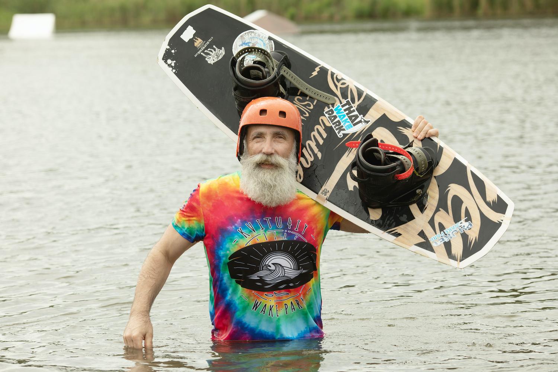 Bearded man holding wakeboard.