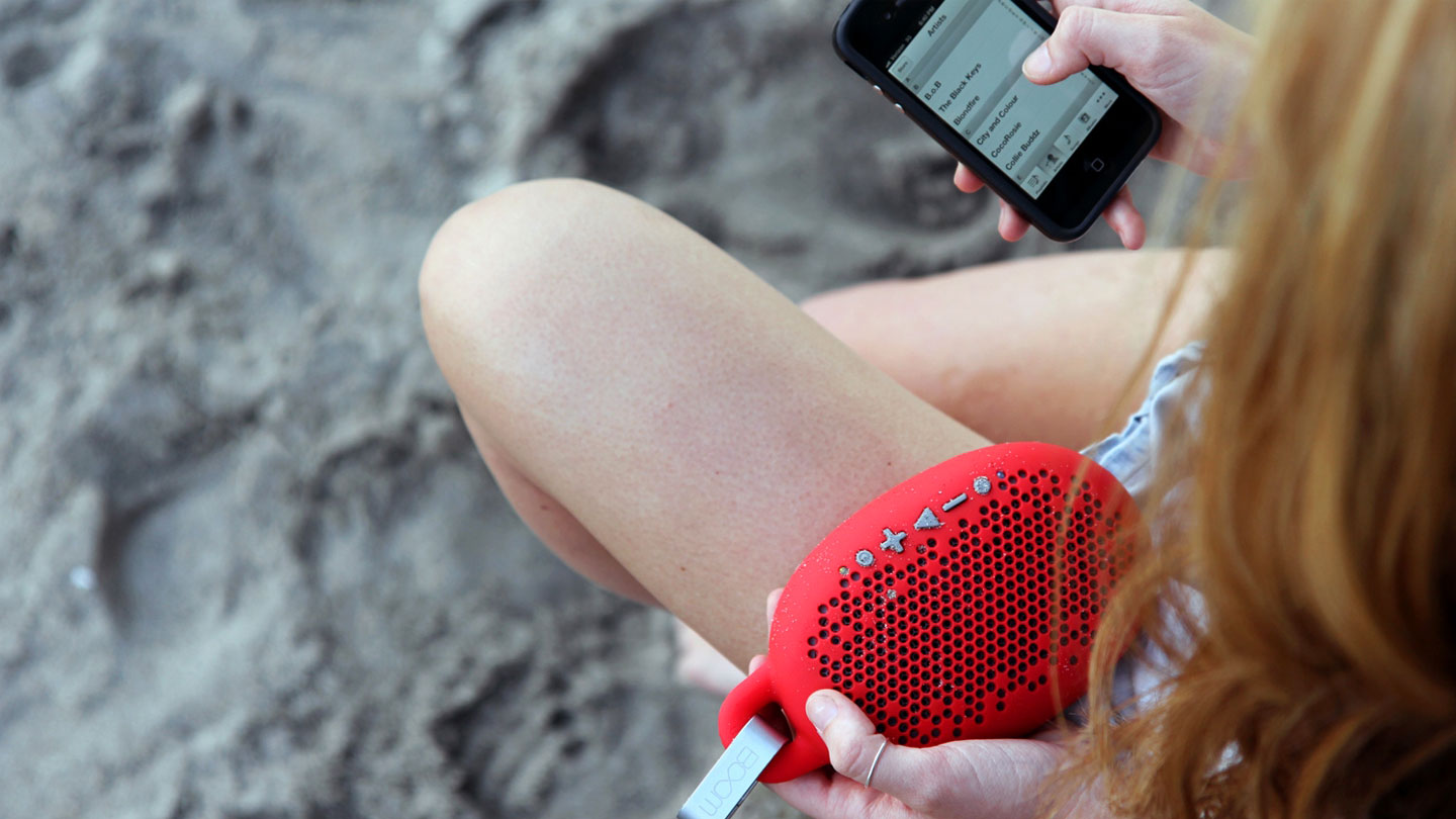 Young girl connects with dust-proof Boom bluetooth speakers on phone