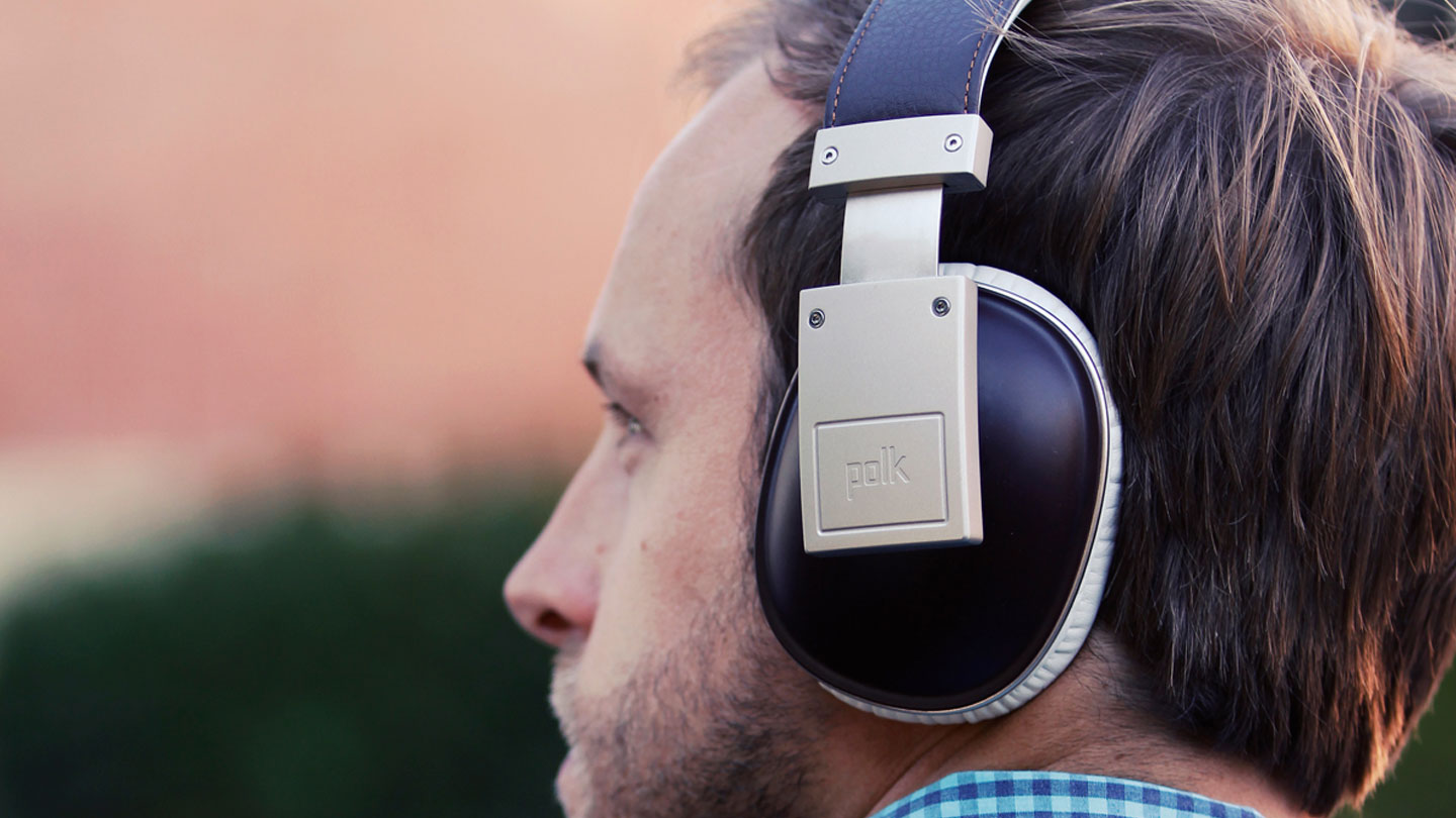 A man listening on Polk Audio headphones, heritage brand design with state-of-the-art technology