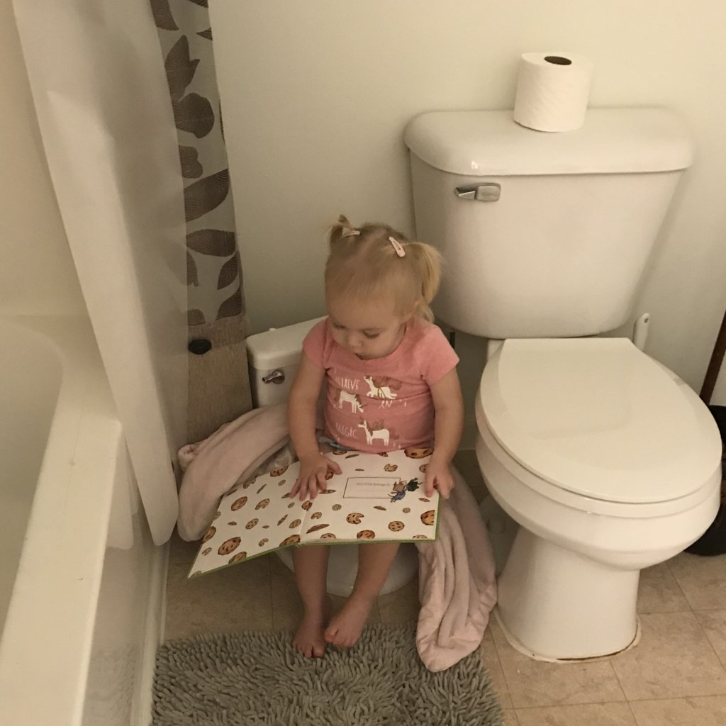 One year old on potty seat reading