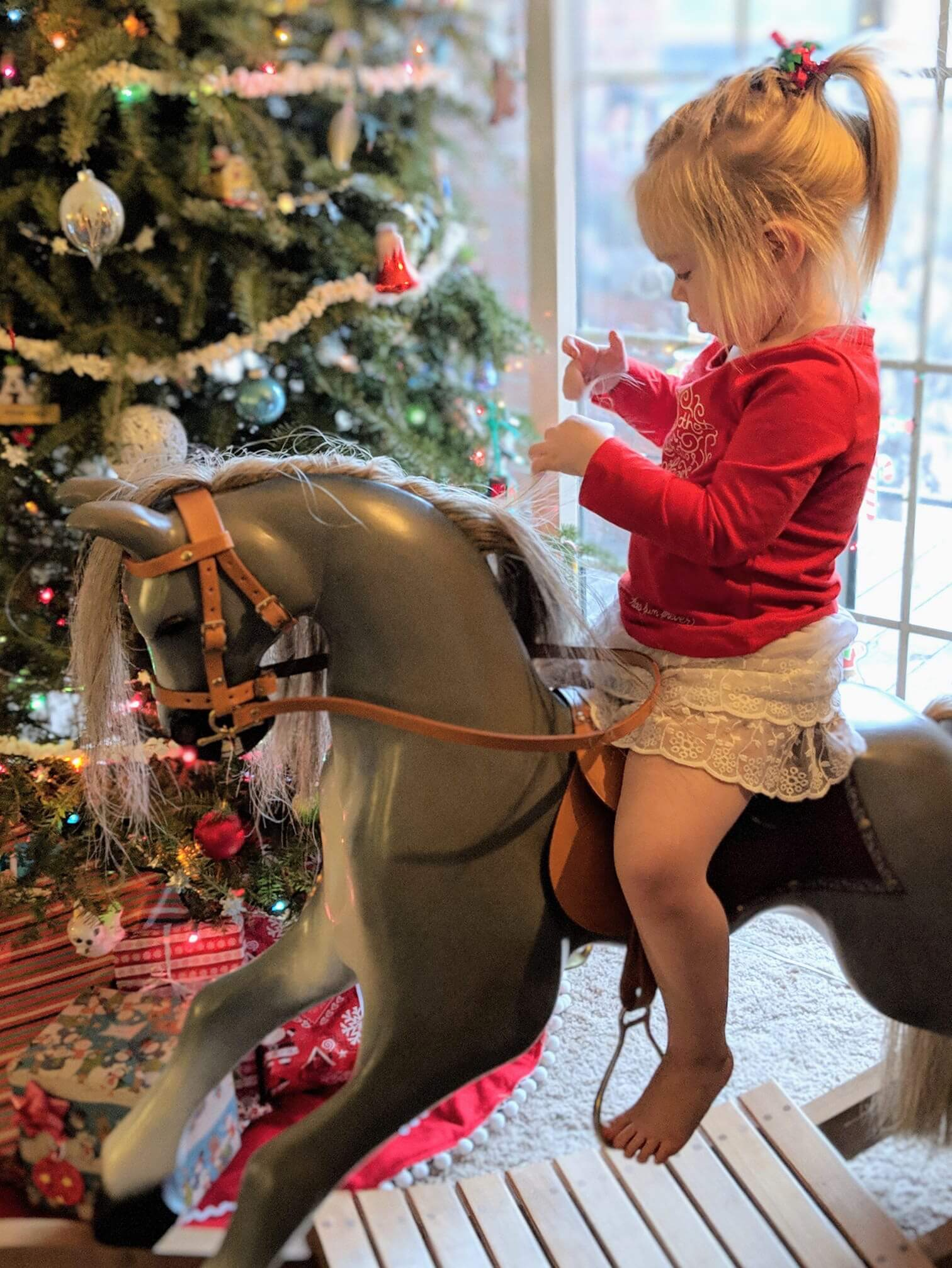 2 year old girl on a hand carved rocking horse in front of a Christmas treee