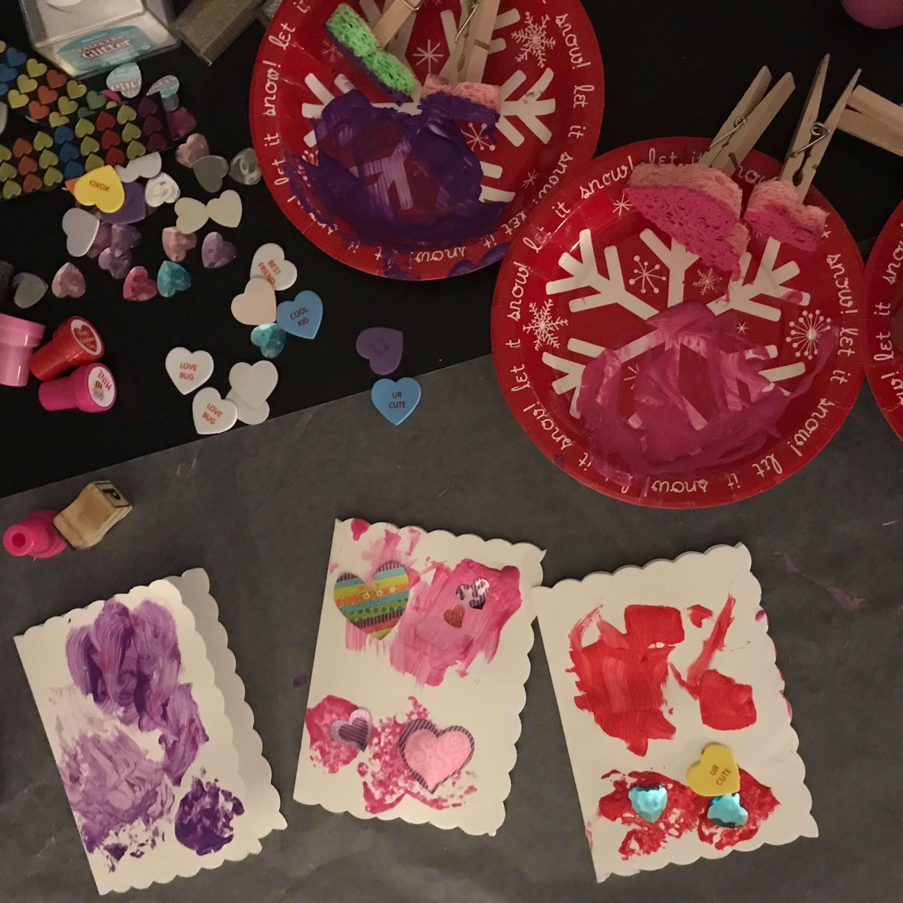 3 Valentine's Cards in the process of being made. They are surrounded by a variety of stickers, gems and other craft supplies.