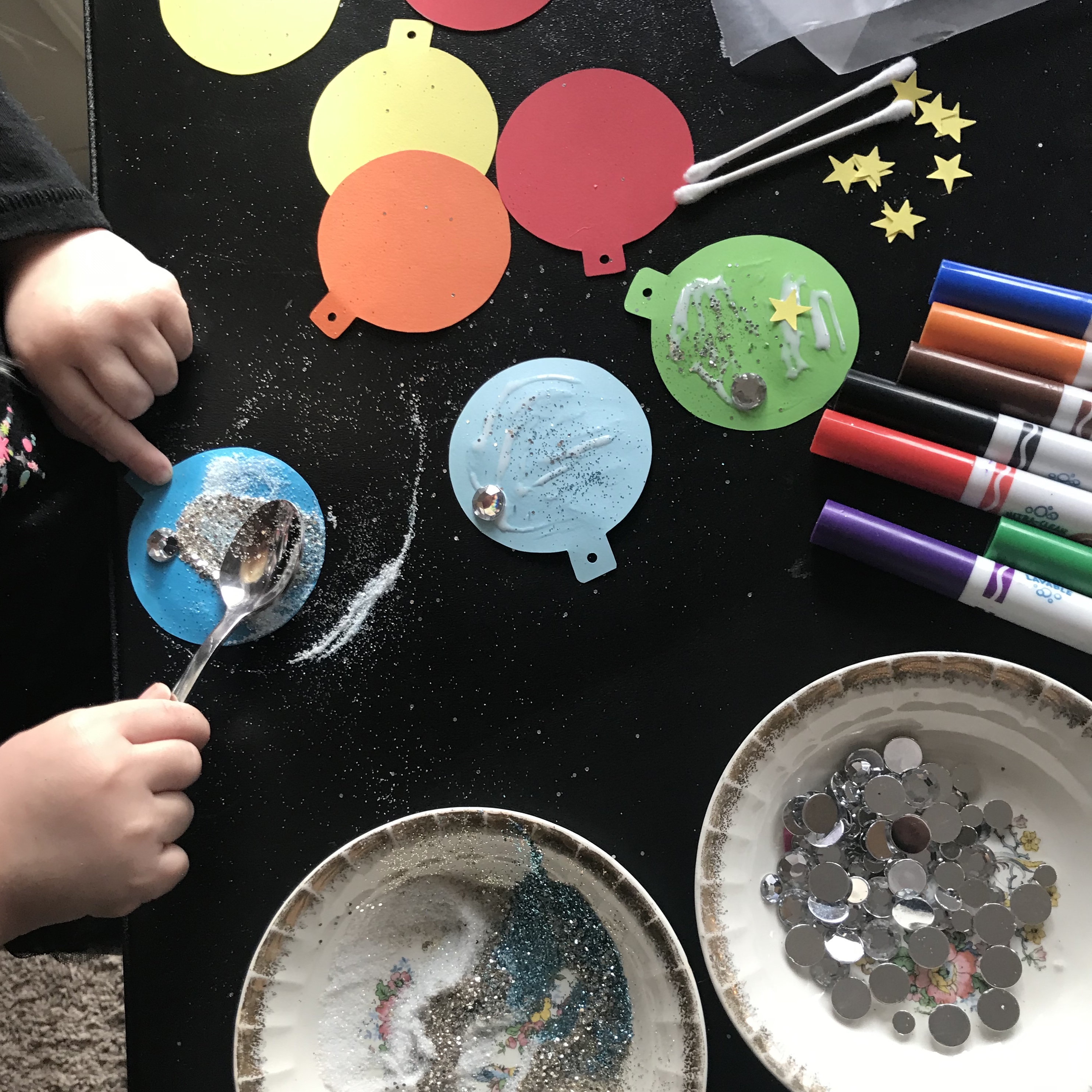 Toddler hands using spoon to put glitter on Christmas tags
