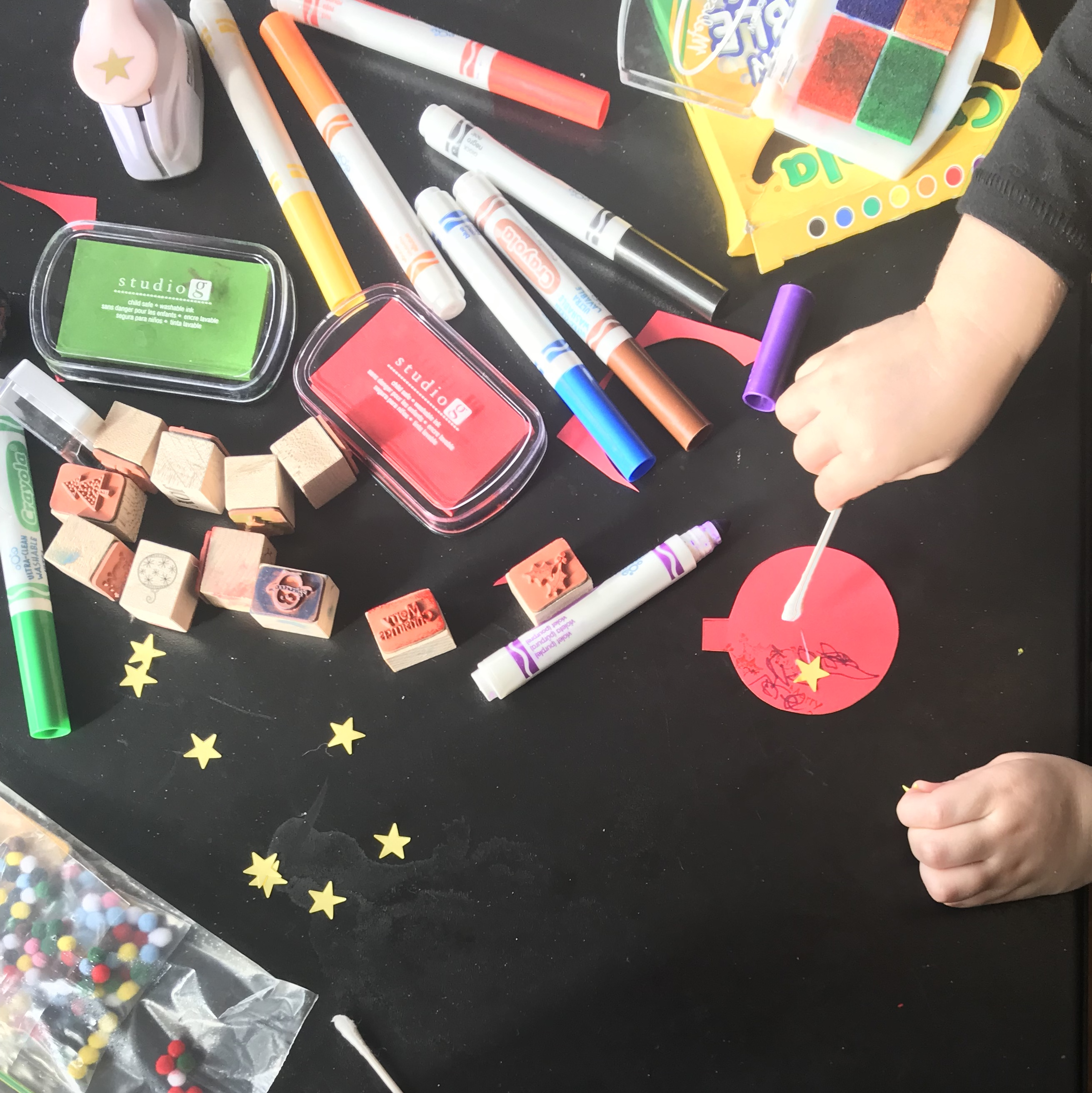 Toddler hands using q tip to apply glue, various art supplies spread out on table