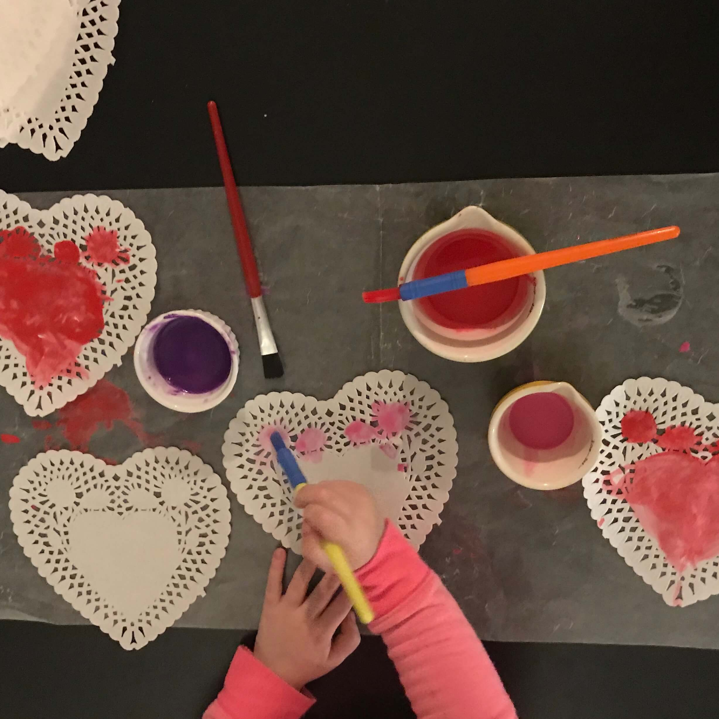 Toddler painting heart shaped doilies