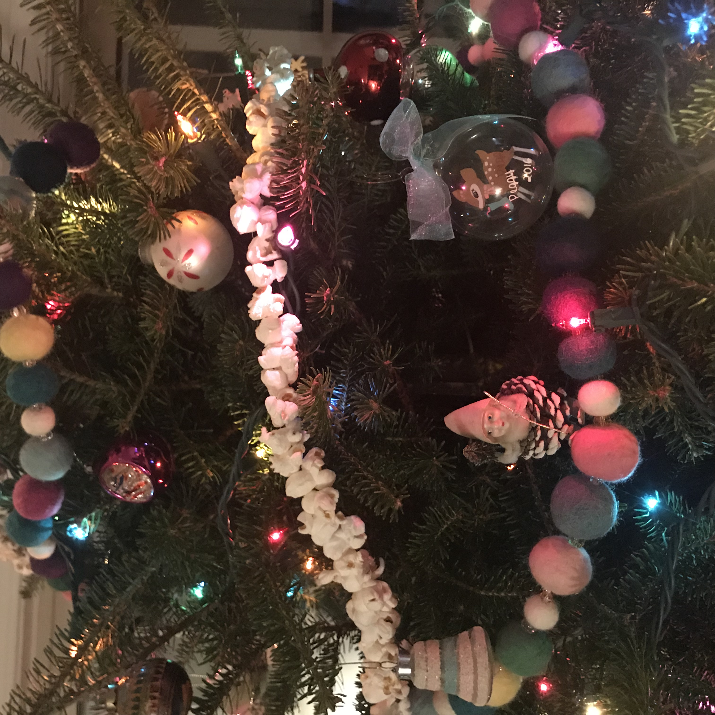 Felt ball garland hanging on lit tree with other decorations
