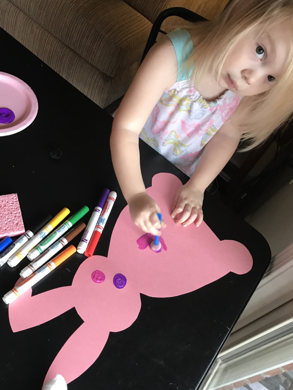 3 year old girl painting pink construction cutout of a bunny