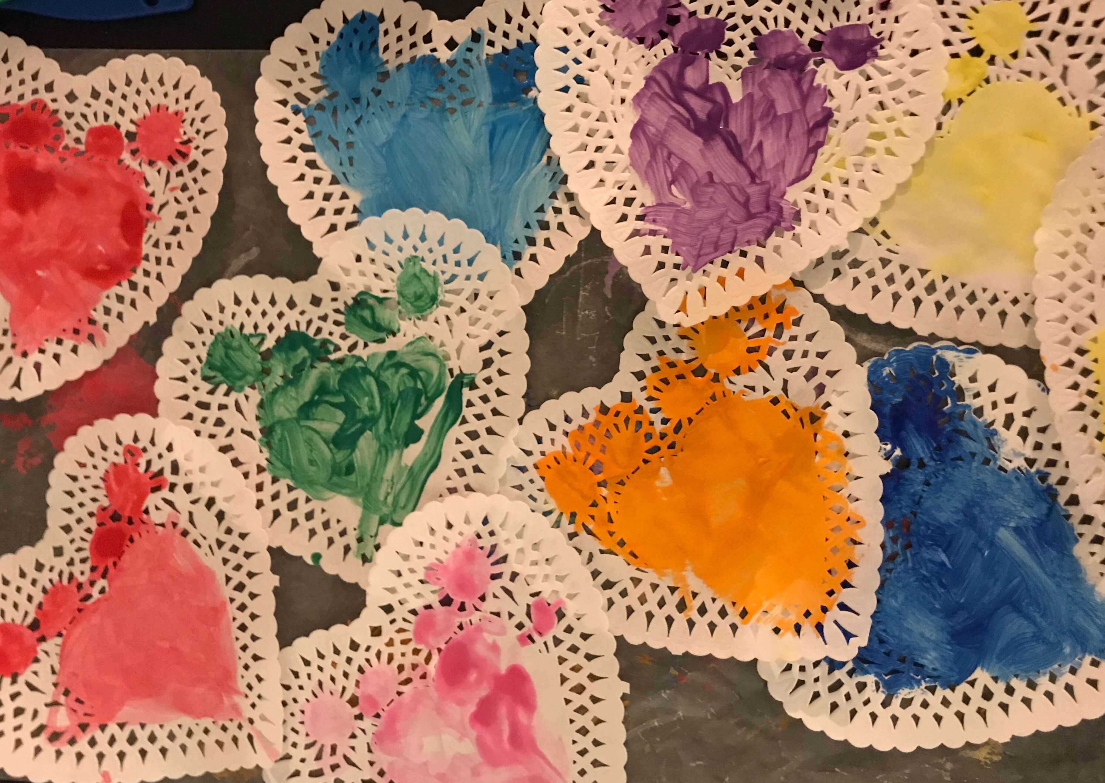 Assorted heart shaped doilies painted in different colors as a Valentine's Craft for Toddlers