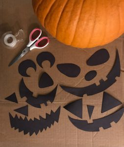 Pumpkin, sizzors, tape, and cut out jack-o-lantern mouths, noses, and eyes