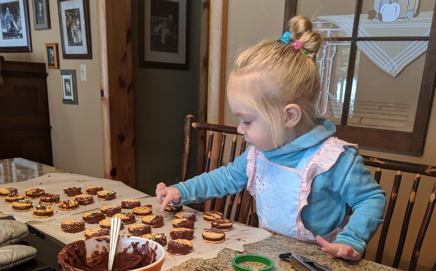 Toddler making chocolate covered ritz crackers with York patties, Christmas cookie family traditions
