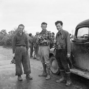 Three men pose holding cameras