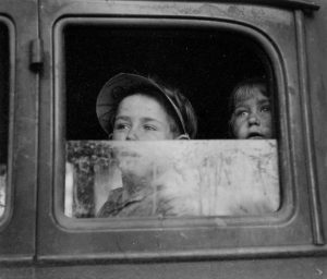Two boys stare out of car window