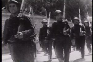 Men with rifles march
