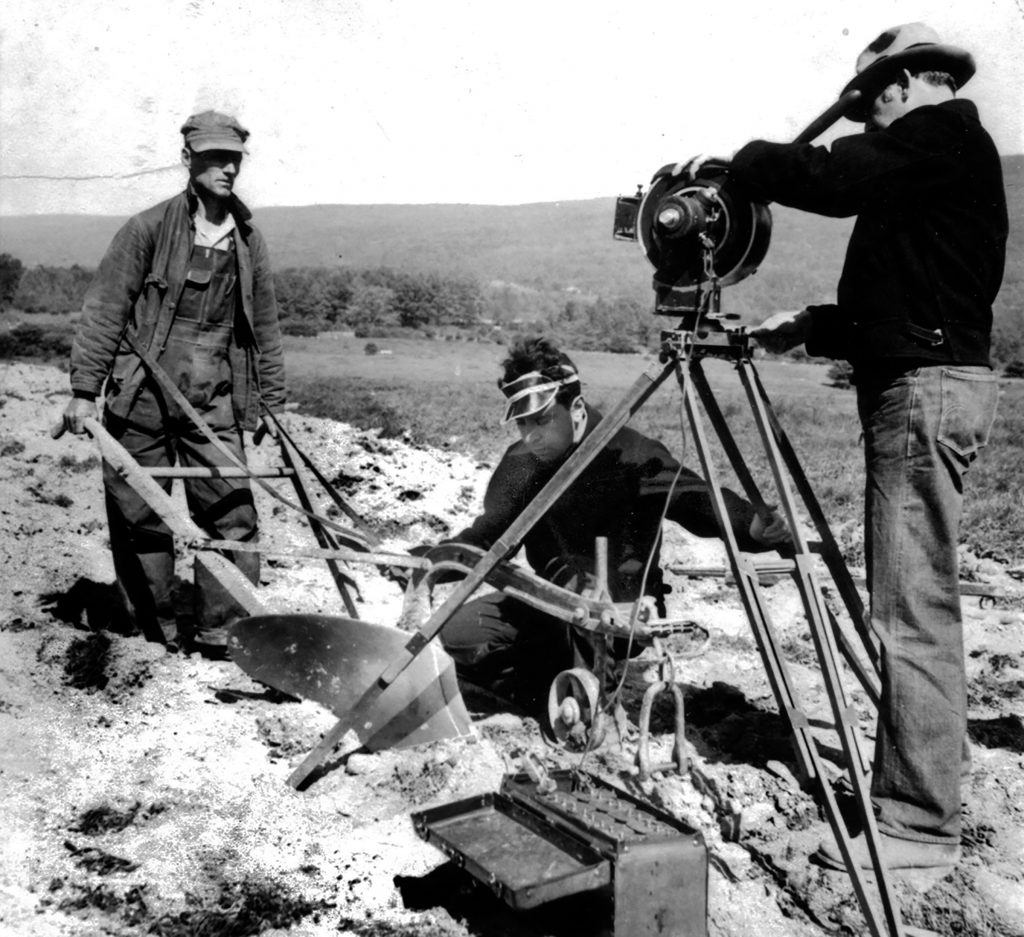 Camera, two camera crew, farmer with plow