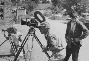 Two men at cameras, a third looks away