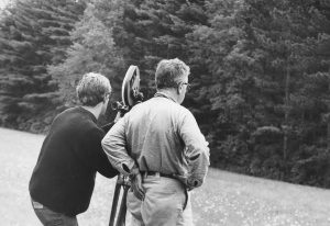 Two men, backs to camera film with camera