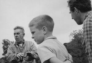 Man talks to two actors in foreground