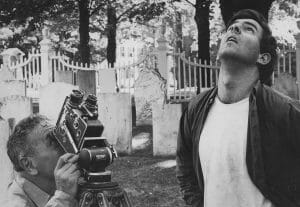 Two men look up, one behind a movie camera