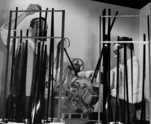Two men work with 16mm film and editing machine