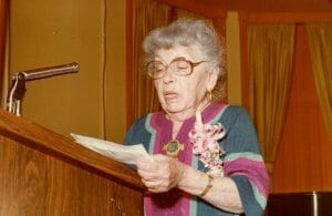 Elderly woman speaks at podium