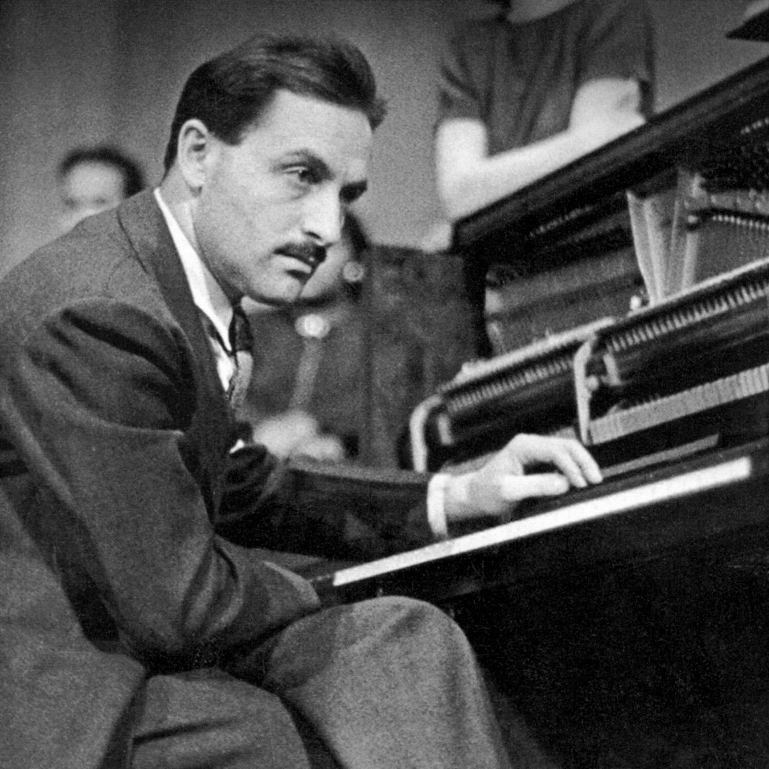 Young moustached man at a piano