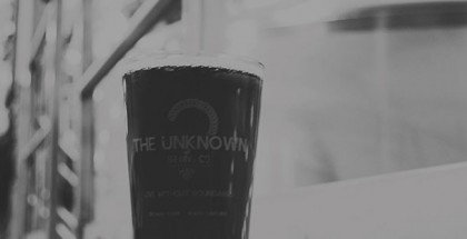 Black and white photo of a pint glass of beer in an industrial setting.