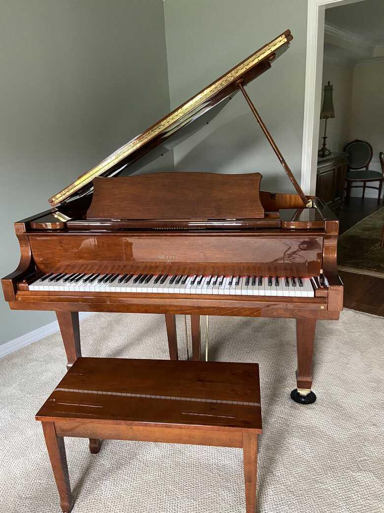 Baby grand piano with polished walnut finish