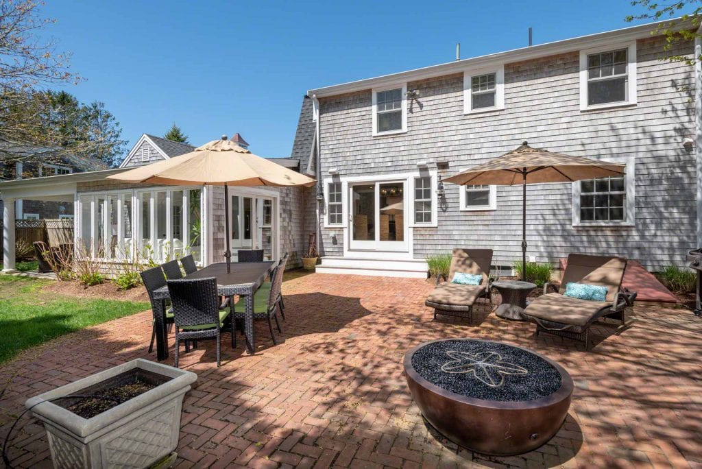 Indoor-Outdoor Living Hub Brick Patio With Dining, Lounging And Fire Pit Areas Katama Farmhouse For Sale Martha's Vineyard Real Estate