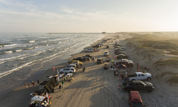 An_aerial_view_of_South_Padre_Island_with_people_parked_and_driving_on_the_beach.jpg