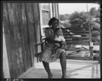 Mrs._Aron_Conway_and_baby_swinging_on_porch_of_their_home_in_company_housing_project._Adams__Rowe___Norman_Inc...._-_NARA_-_540599.jpg