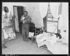 Eddie_Cain__miner__looking_over_his_bills_in_his_home_in_company_housing_project._Adams__Rowe___Norman_Inc.__Porter..._-_NARA_-_540596.jpg
