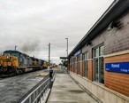 Maywood_IL_Commuter_Station_with_CSX_freight_train.jpg