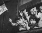 Bainbridge_Island__Wash.__evacuation_--_Group_of_young_evacuees_wave_from_special_train_as_it_leaves_Seattle_with_Island_evacuees__March_30__1942.jpg