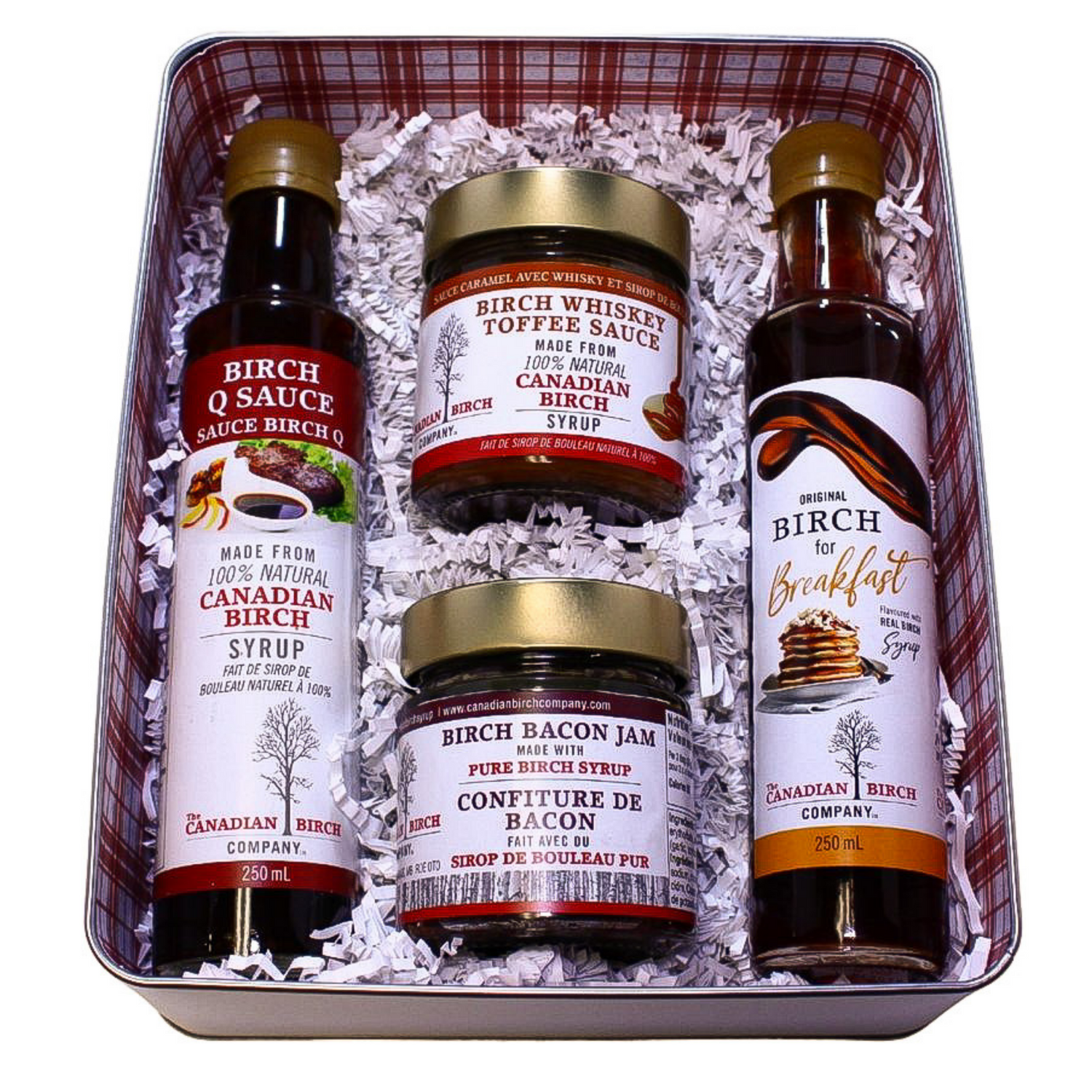 A silver tin box with window lid, and products nestled inside with crinke paper. Included are Birch Bacon Jam, Birch Whiskey Toffee Sauce, Birch Q Sauce and Birch for Breakfast syrup.
